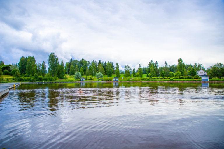 Kesäisessä kuvassa henkilö uimassa, rannalla siniset pukukopit.