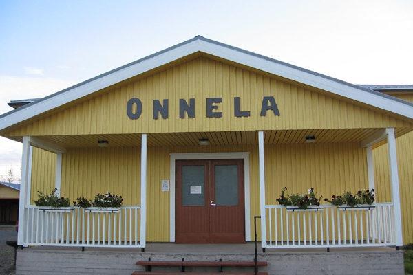 Keltainen puinen rakennus, edestä päin kuvattuna. Oven edessä iso terassi, oven yläpuolella teksti Onnela.