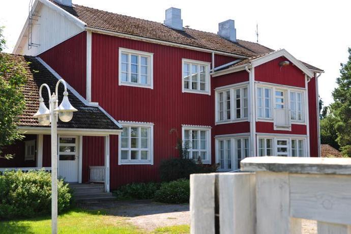 Punainen kaksikerroksinen talo etuviistoon kuvattuna, etualalla valkoinen aita, vasemalla laidassa valotolppa.