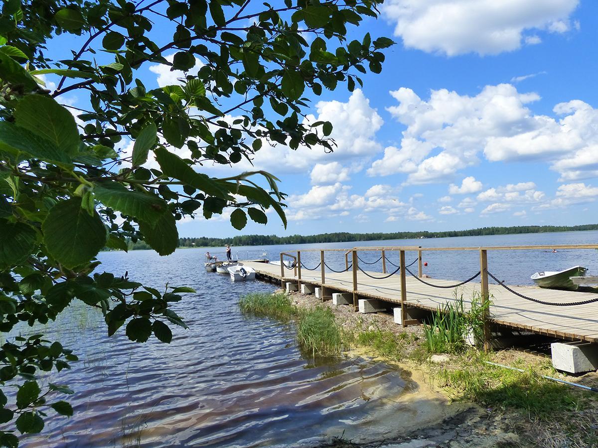 Pitkä puinen laituri järven rannassa, jossa on köysikaiteet. Taka-alalla sininen pilvinen taivas.
