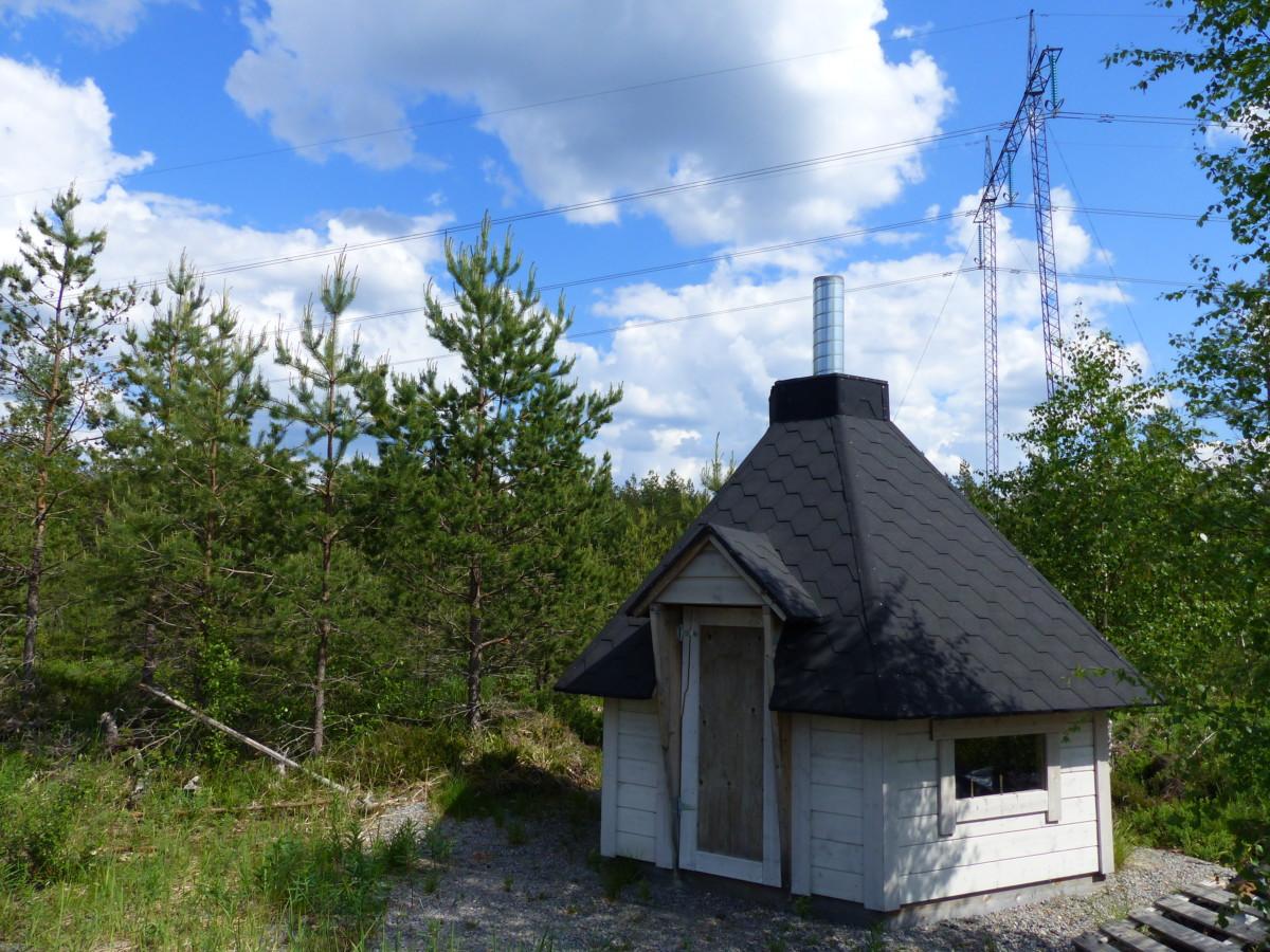 Valkoinen huopakattoinen kota kesäisessä metsä maisemassa. Taka-alalla näkyy sininen taivas ja iso sähkölinja.
