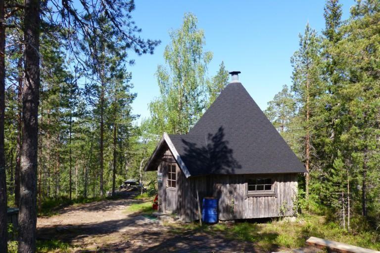 Havumetsässä kallion päällä harmaasta puusta tehty kota, jossa musta huopakatto.