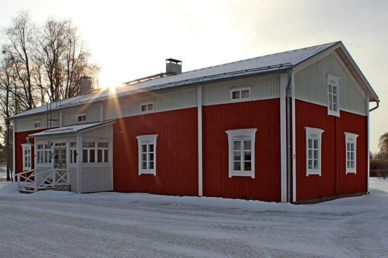 Talvinen kuva punavalkoisesta puurakennuksesta, kuvattu etuviistoon.