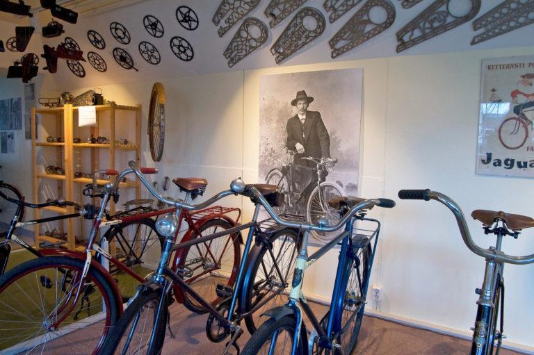 Kuva museon sisältä, etualalla viisi polkupyörää, seinällä kulisteita ja polkupyöräosia.