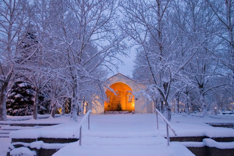Talvinen kuva teuvan Rauniokirkosta, etualalla lumisia puita joitten takana valaistu Rauniokirkko jonka sisällä on joulukuusi.