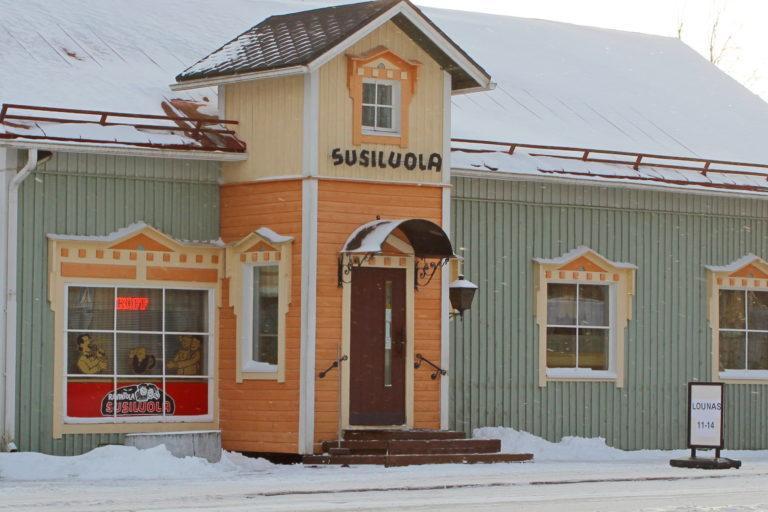 Vihertänä puinen rakennus, jossa susiluolan logoja.