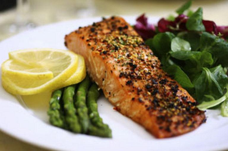 Ruokalautanen, jolla on kalaa, vihanneksia ja sitruunaviipaleet.
