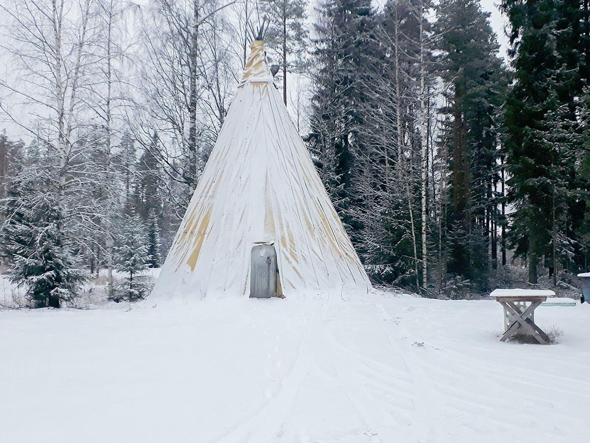Keltapressuinen kota kuvattuna talvella, kuvassa luminen laavu keskellä ja pieni pöytä oikealla reunassa.