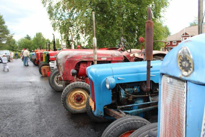 Kuvassa jonossa vanhoja eri värisiä traktoreita.