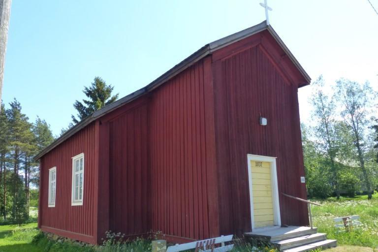 Punainen vanha rakennus. Keltainen ovi ja risti katolla.