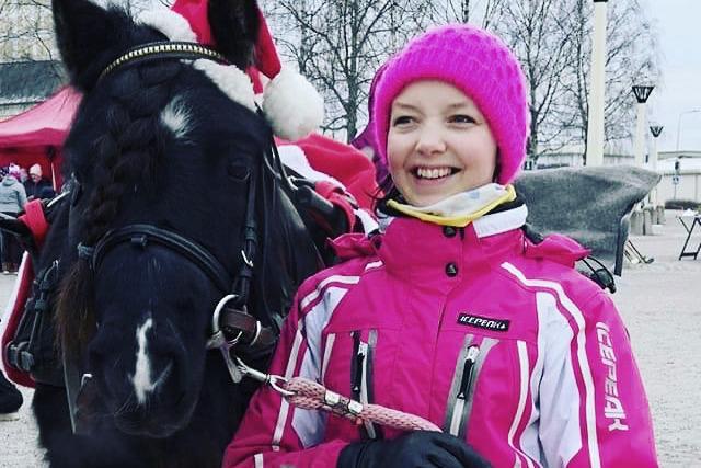 Kuvassa poni ja nainen, ponilla on tonttulakki ja nainen hymyilee.