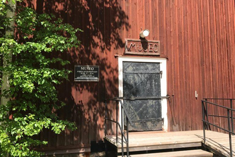 TEuvan kotiseutumuseon ovi, oven vieressä museon aukioloista kertova kyltti.