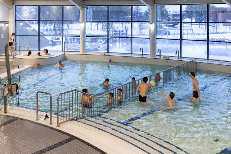 Uimahallin altaat, jossa useita henkilöitä uimassa