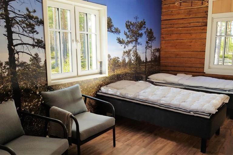 Kuvassa kaksi tuolia ja kaksi sänkyä, seinässä maisematapeetti ja ikkuna.