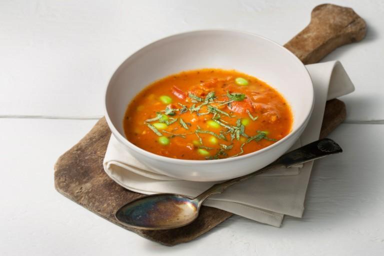Keittolautanen, jossa tomaattista keittoa. Kuvassa myös puinen tarjotin.