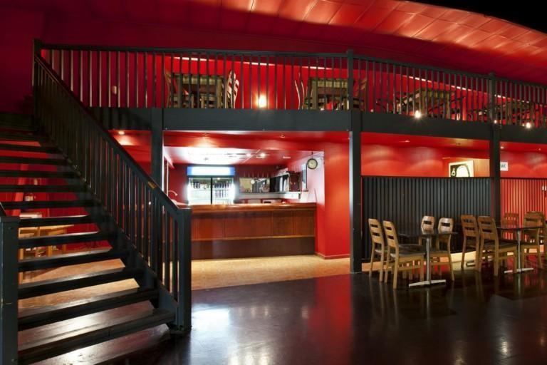 Sisäkuva tanssiravintolan baaritiskista, elualalla pöytäryhmiä javasemmalta nousevat portaat parveen jossa myös istumapaikkoja.