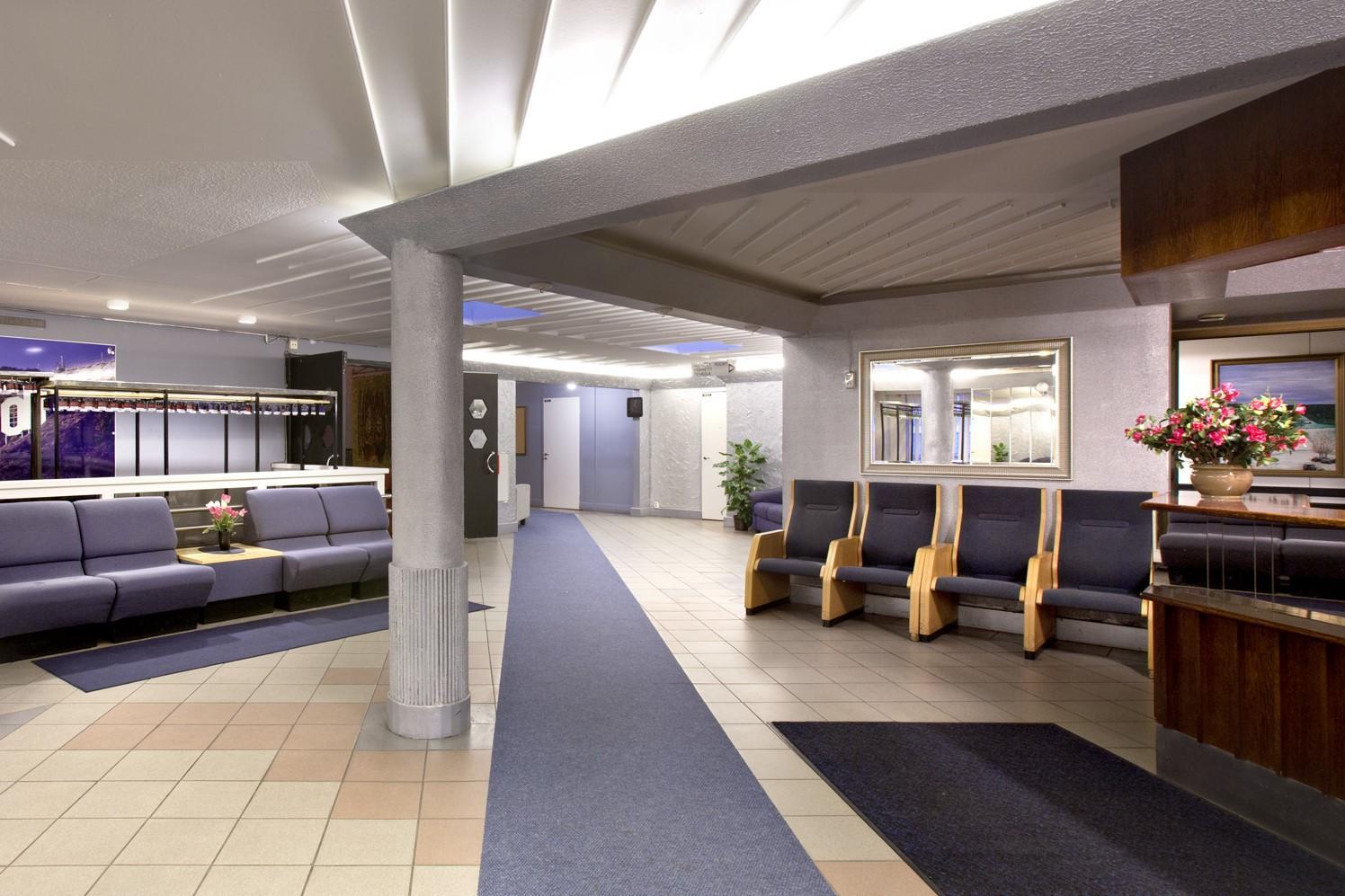 Aronkeitaan sisääntuloaula, lattialla mattoja, seinän vierustassa nojatuoleja ja oikealla etualalla tiski.