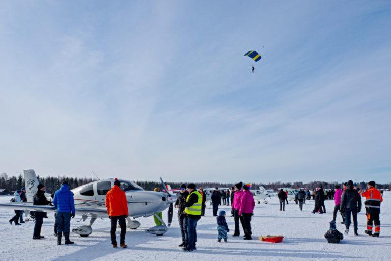 Flyin tapahtumakuva, talvikuvassa liitovarjo sinisellä taivaalla, maassa ihmisiä ja lentokoneita.