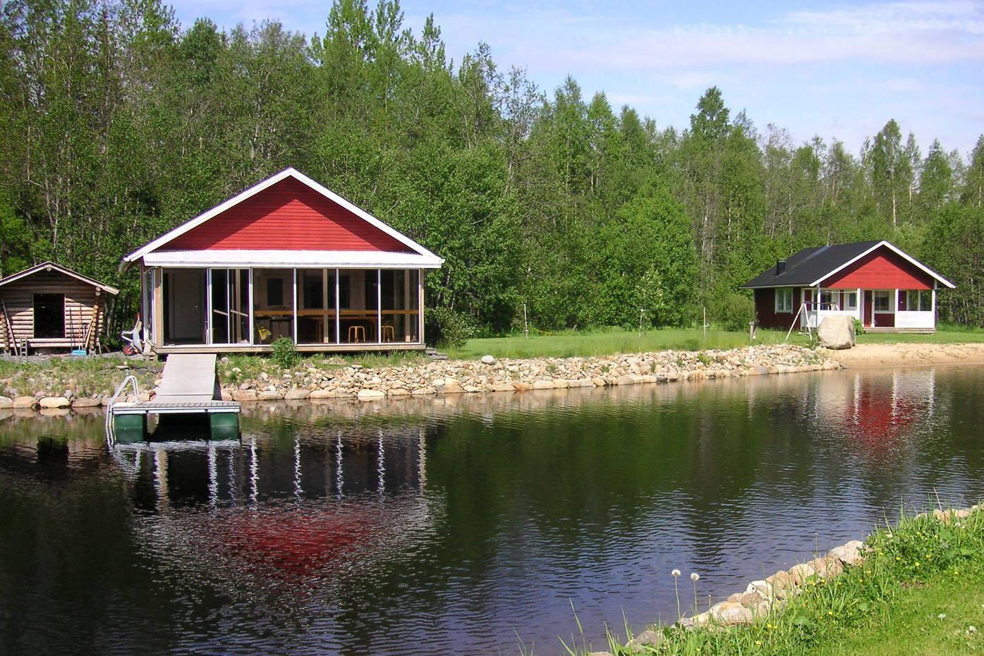 Etuallalla lampi, jonka takana kaksi punaista mökkirakennusta.