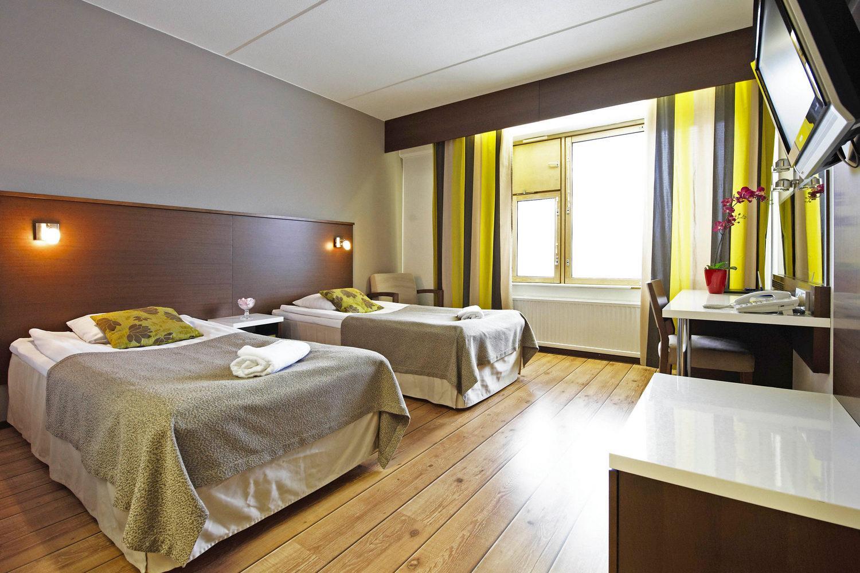 Sisäkuva hotellihuoneesta jossa kaksi sänkyä, pöytä ja televisio.