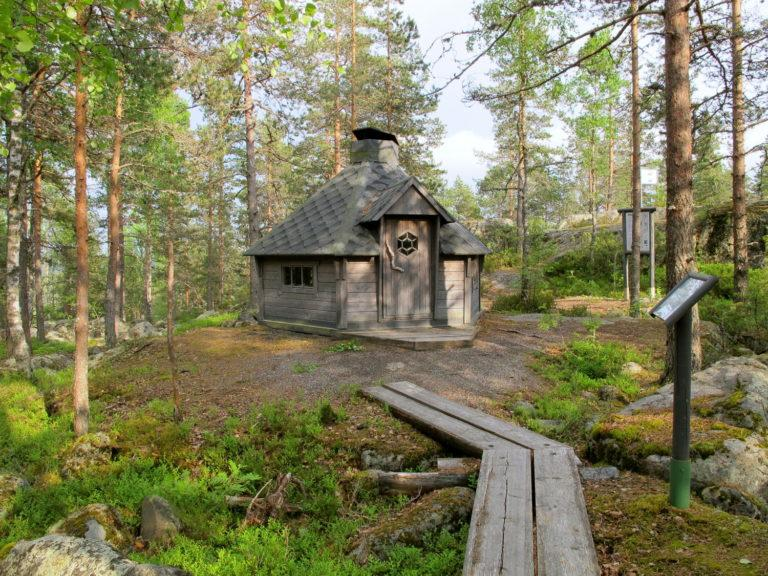 Iso-Kakkorin hirsinen kota ja sille johtavat pitkospuut sekä opasviitat, kota kuvattu edestä päin, etualalla pitkospuut.