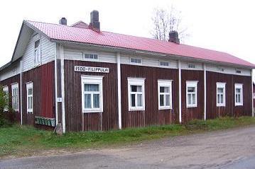 Kuvassa vanha puna-valkoinen maalaistalo.