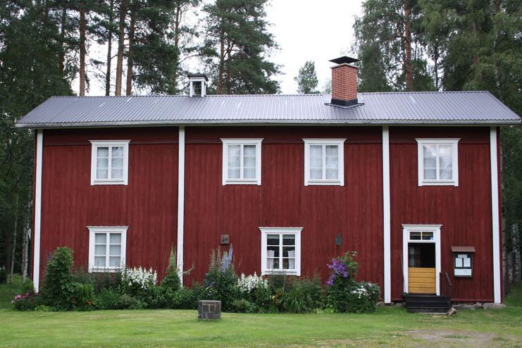 Punainen kaksikerroksinen maalaistalo edestä päin kuvattuna.
