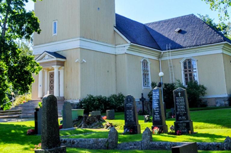 Keltainen puinen kirkkorakennus etuviistoon kuvattuna, etualalla hautakiviä.