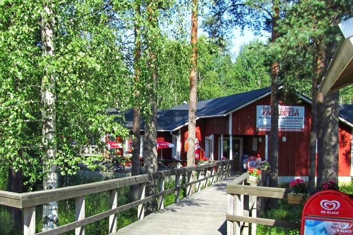Etualalla puiset kaiteet ja polku, taka-alalla punainen puinen ravintolahuone.
