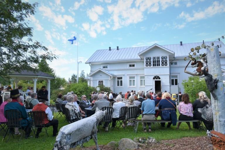 Valkoinen kaksikerroksinen puinen rakennus edestä kuvattuna, etualalla paljon ihmisiä istumassa. Suomen lippu on nostettu salkoon.