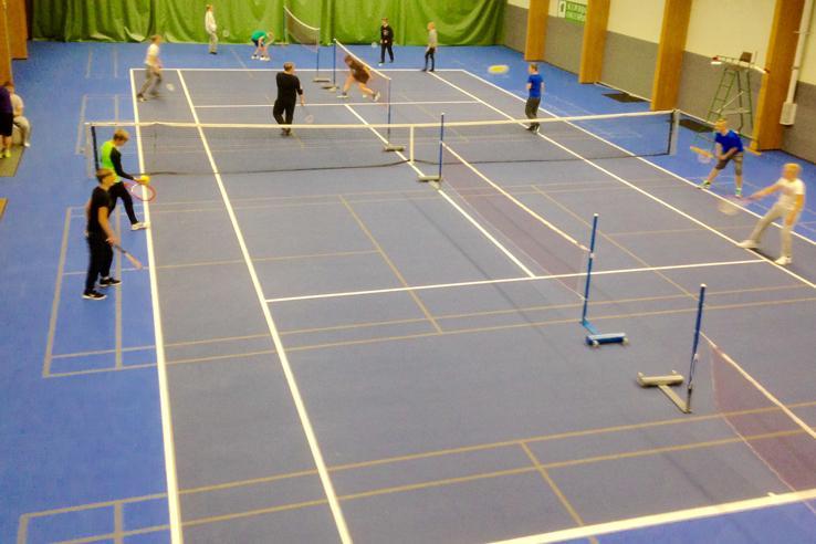 Kuva tennishallisn sisältä, kentällä muutamia pelaajia.