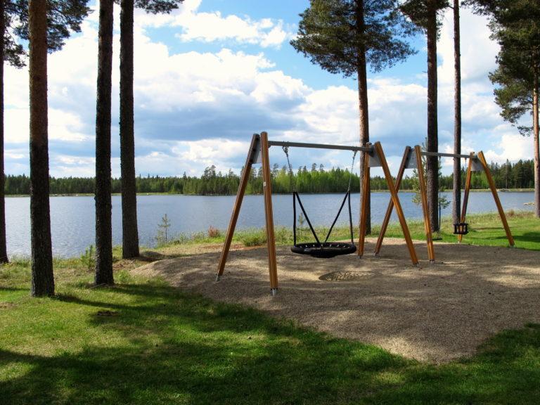 Kesäisessä kuvassa etualalla lasten hämähäkkikeinu, taustalla siintää Säläisjärvi.