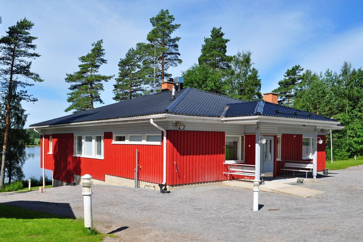 Kuvassa punainen yksikerroksinen rakennus etuviistoon kuvattuna.