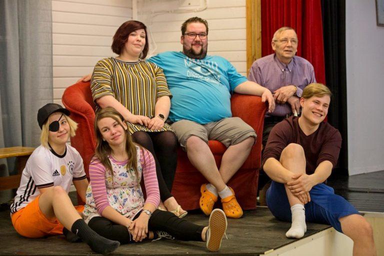 Kuusihenkinen näytelmäryhmä istuu lavan reunalla, kaikilla on iloiset ilmeet.