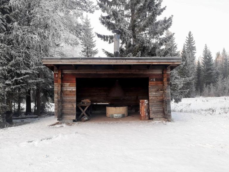 Talvisessa kuvassa hirsinen laavu kuvattu suoraan edestä. Laavun sisällä on tulipaikka ja laavun takana kasvaa puita.