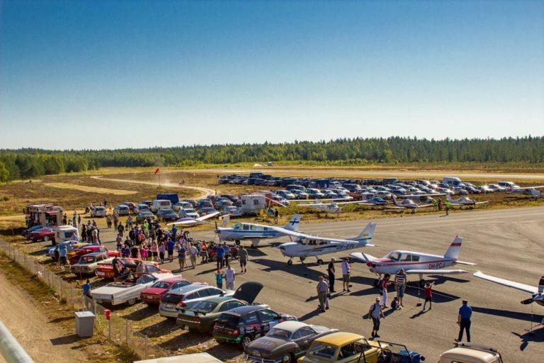Kuva Konerieha tapahtuma-alueelta. Kesäisessä kuvassa on paljon vanhoja autoja, lentokoneita ja ihmisiä.