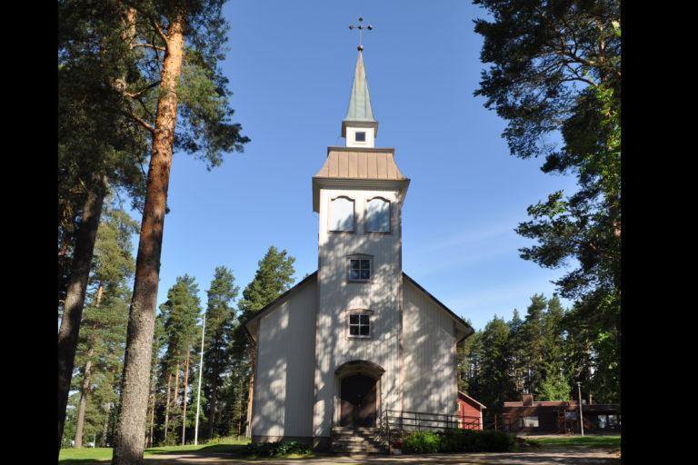 Keltainen puinen kirkkorakennus suoraan edestä kuvattuna.