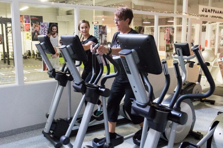 Kuva kuntosalin sisätiloista, kuvassa kaksi henkilöä treenavat crosstrainereilla.