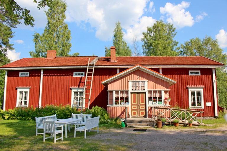 Punainen rakennus edestä päin kuvattuna, talon edessä valkoiset puutarhakalusteet.