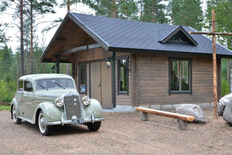 Etualalla vanha vihreän värinen auto, jonka takana ruskea hirsinen rakennus. Kuvassa oikealla puinen penkki ja risti.