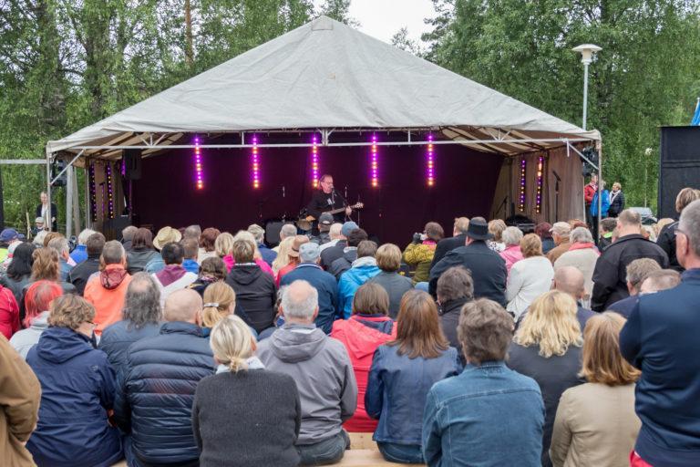Tapahtumakuva Lauhan Speleistä, meis ja kitara esiintymisteltassa jonka enessä iso joukko ihmisiä.