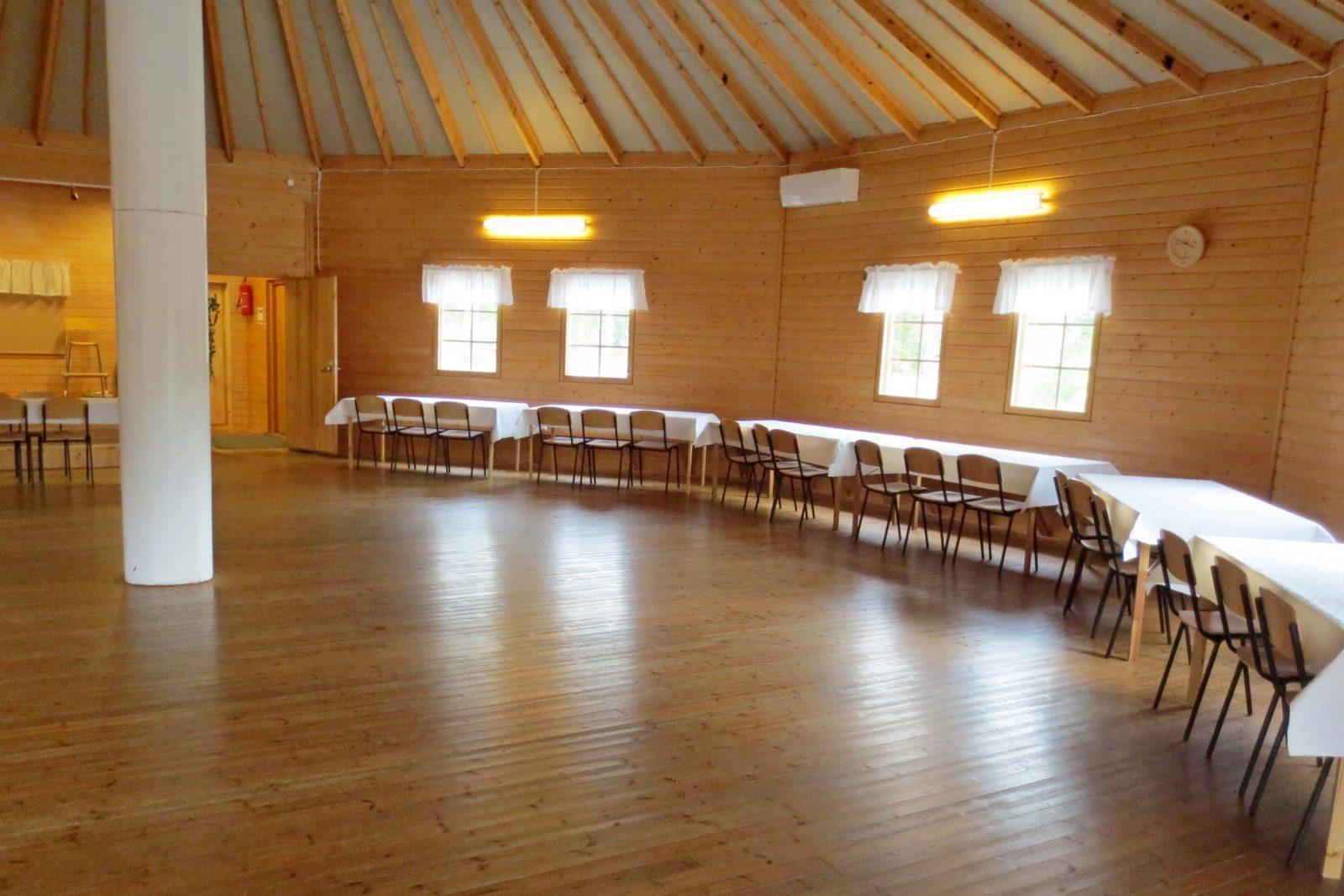 Sisäkuva juhlasalista, keskellä tolppa, seinien vieressä pöydät ja tuolit.
