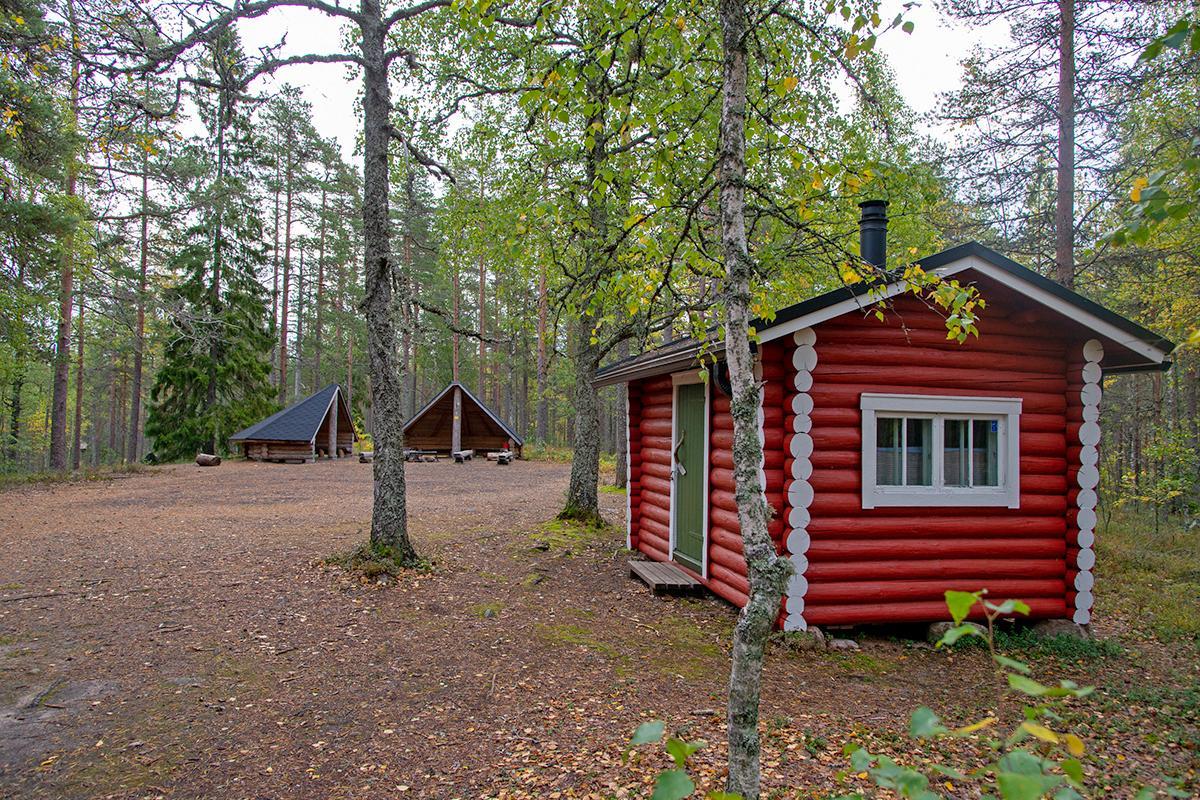 Pieni punainen hirsinen mökki, taka-alalla kaksi laavua.