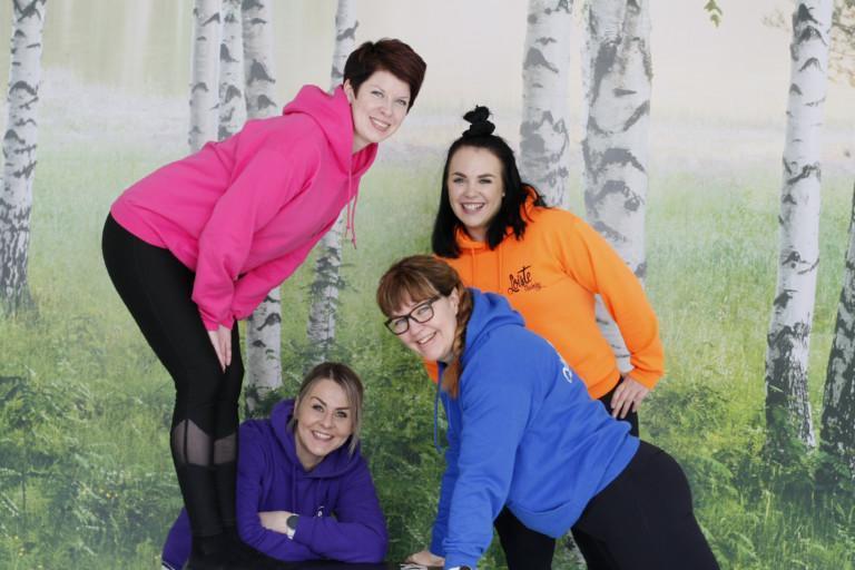 Ryhmäkuvassa olevat neljä naista ovat pukeutuneet eri värisiin paitoihin. Naiset katsovat kohti kameraa ja hymyilevät.