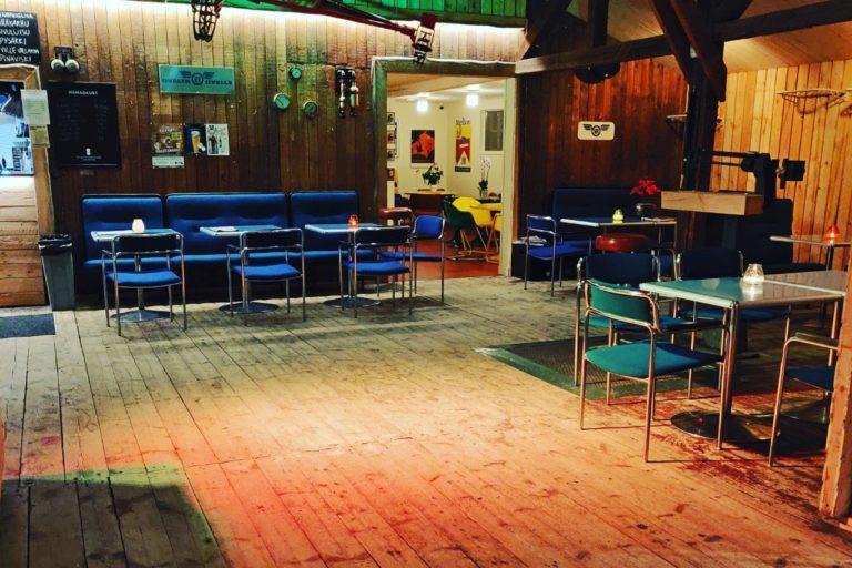 Sisäkuva Makasiinin baarista, kuvassa pöytiä ja tuoleja sekä seinillä tauluja.