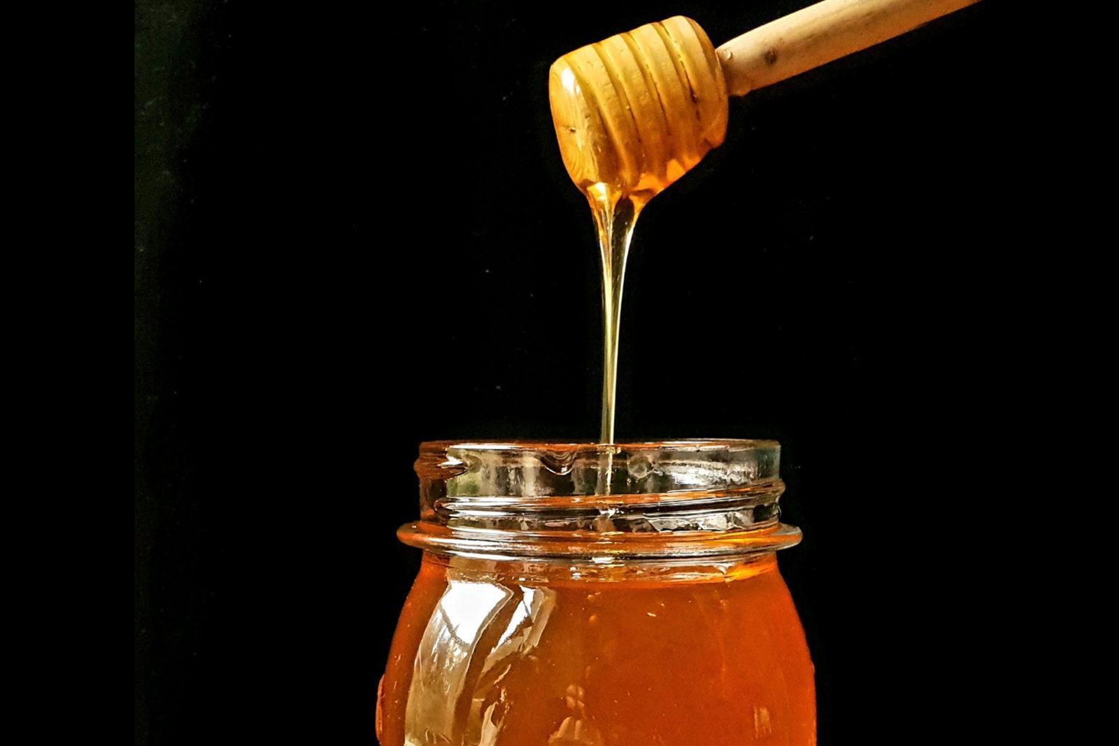Hunajapurkki ja hunajatikku josta valuu juoksevaa hunajaa.