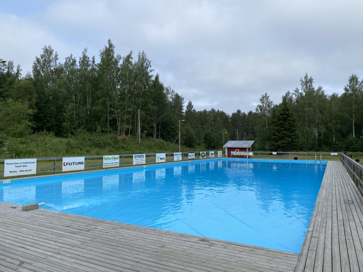 Kuvassa maauimala. Iso sininen allas keskellä kuvaa, jossa ympärillä puinen terassi. Vasemmassa reunassa sponsorikylttejä.