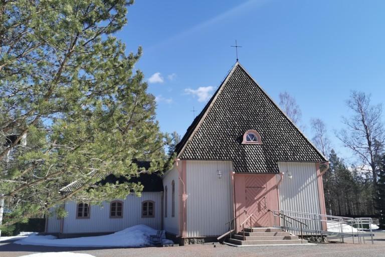 Puinen kirkko etuviistoon kuvattuna. Etualalla mänty.