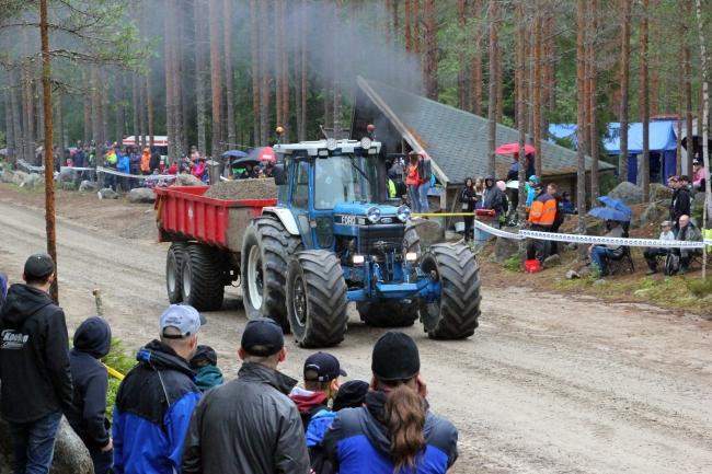 Mäkivetokisakuva, etualalla ja taka-alalla ihmisiä katsomassa kisaa, keskellä sininen traktori ja punainen santakuormainen peräkärry.