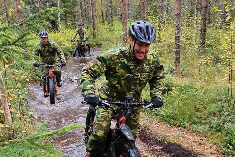 Maastopukuiset ja kypäräpäiset henkilöt ajavat maastopyörillä metsätiellä, jolla on isoja vesilätäkköitä.
